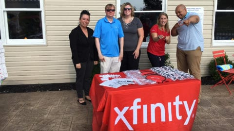 group of people posing by a comcast table