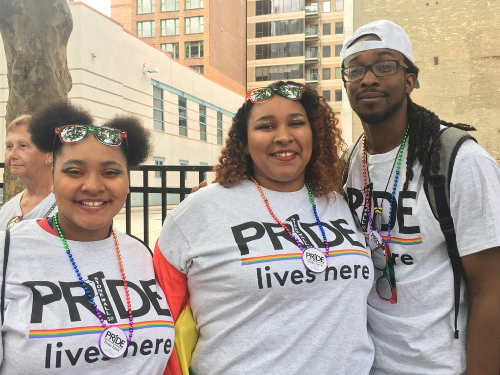 """Three Comcast employees wearing shirts that say """"Pride lives here."""""""