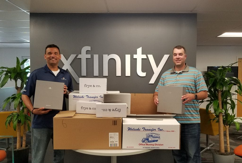 Two Comcast employees holding boxes of donated shoes