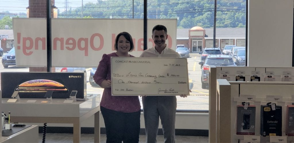 Employee from Lauri Ann West Community Center accepts $1,000 check from Comcast employee