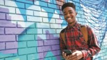 teen boy holding smartphone, leaning against colorfully painted wall