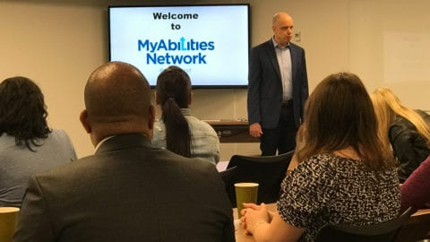 Tom Wlodowski speaking in front of a group of employoees with MyAbilities Network logo on a screen behind him