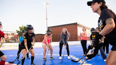 Jocelyne Lamoureux-Davidson and Monique Lamoureux-Morando play hockey with Internet Essentials participants.