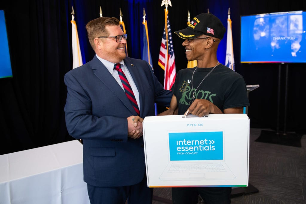 smiling man shaking the hand of a military veteran while handing him a laptop