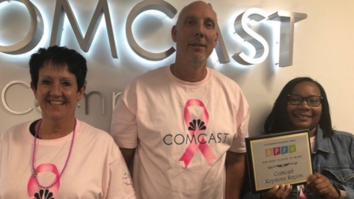 employees holding a plaque in front of Comcast logo
