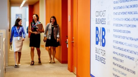 Women walking down a hallway past a Comcast Business logo
