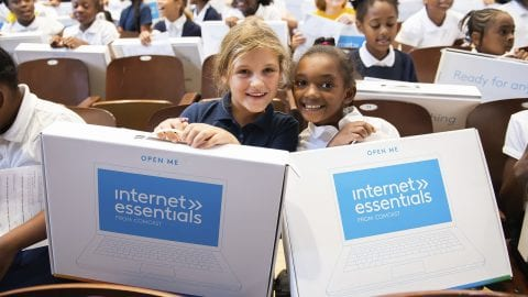 two girls holding Internet Essentials laptops at Comcast event