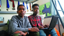 two high school-aged boys working on a laptop in a bedroom