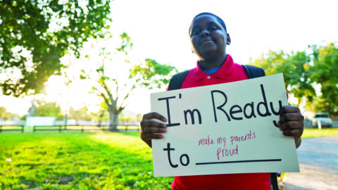 """Boy holding sign that says """"I'm ready to make my parents proud"""""""