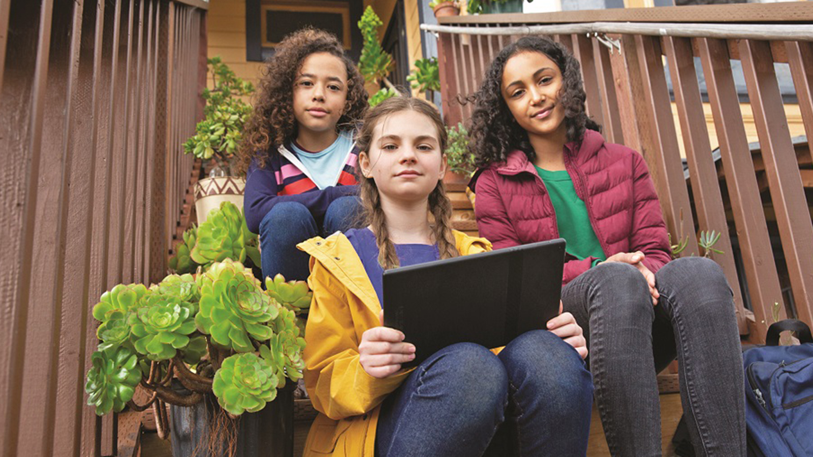 three girls sitting on steps looking at a laptop.