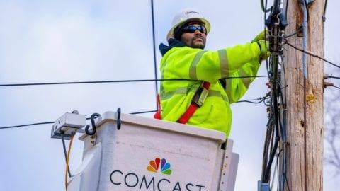 Comcast technician installing line on pole